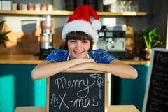 Empregada de mesa de sorriso que veste um chapéu de Santa e que senta-se com uma placa do sinal X-mas Fotos de Stock