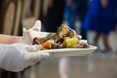 A empregada de mesa está guardando um prato: carne com vegetais grelhados fotos de stock royalty free