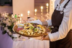 A empregada de mesa está guardando um prato de madeira com carne e queijo fotografia de stock royalty free