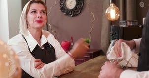 A empregada de mesa loura nova da mulher diz uma história ao barman filme