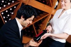 A empregada de mesa oferece um frasco do vinho vermelho Imagens de Stock Royalty Free
