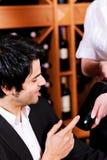 A empregada de mesa oferece um frasco do vinho vermelho Fotografia de Stock