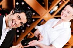 A empregada de mesa oferece um frasco do vinho vermelho Fotos de Stock
