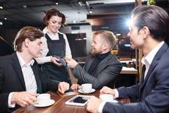 Empregada de mesa positiva que dá o terminal do pagamento aos convidados do negócio dentro imagens de stock