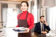 Empregada de mesa positiva que leva pratos sujos afastado imagens de stock royalty free