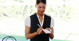Empregada de mesa que escreve para baixo a ordem no bloco de notas vídeos de arquivo
