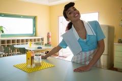 Empregada de mesa que está no contador fotografia de stock