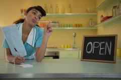 Empregada de mesa que está no contador no restaurante fotografia de stock