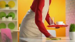 Empregada de mesa que limpa a tabela do café que remove a bandeja plástica, trabalho baixo-pago, ocupação video estoque