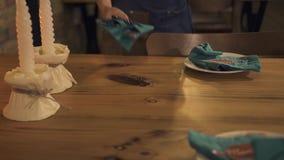 Empregada de mesa que põe a cutelaria sobre a tabela servida para nivelar o jantar com vela no restaurante luxuoso Serviço da emp filme