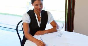 Empregada de mesa que senta-se na tabela e que escreve notas video estoque