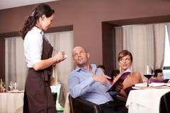 Empregada de mesa que toma o pedido da tabela do restaurante fotografia de stock