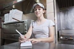 Empregada de mesa que toma o pedido em um restaurante do fast food imagem de stock