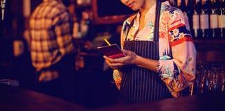 Empregada de mesa que toma uma ordem no bloco de notas no contador imagem de stock