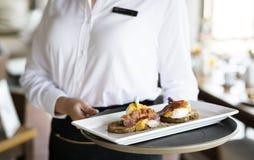Empregada de mesa que trabalha em um restaurante do hotel imagens de stock