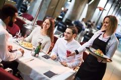 Empregada de mesa que traz a ordem na tabela do terraço no dia de verão Imagens de Stock Royalty Free