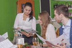 A empregada de mesa recomenda refeições a seus convidados imagem de stock