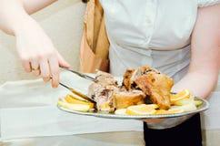 A empregada de mesa serve um prato de fotografia de stock royalty free