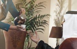 Empregada de mesa Serving Arabic Coffee a um homem árabe rico fotografia de stock royalty free
