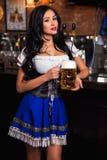 Empregada de mesa 'sexy' nova de Oktoberfest, vestindo um vestido bávaro tradicional, servindo a caneca de cerveja grande Imagens de Stock
