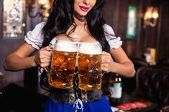 Empregada de mesa 'sexy' nova de Oktoberfest, vestindo um vestido bávaro tradicional, servindo canecas de cerveja grandes na barr Imagens de Stock Royalty Free