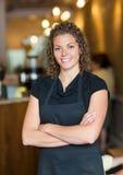 Empregada de mesa Standing Arms Crossed na barra do café Imagens de Stock Royalty Free