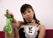 A empregada doméstica asiática 'sexy' guarda uma garrafa do pulverizador Foto de Stock Royalty Free