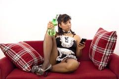 A empregada doméstica asiática 'sexy' olha seu telefone celular Fotografia de Stock Royalty Free