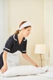 Empregada doméstica das tarefas domésticas que faz a cama na sala de hotel foto de stock