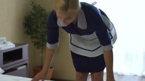 A empregada doméstica loura bonita termina fazer a cama, serviço impecável no hotel de cinco estrelas vídeos de arquivo