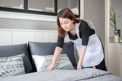Empregada doméstica nova que ordena a cama na sala de hotel, conceito de limpeza do serviço Imagem de Stock Royalty Free