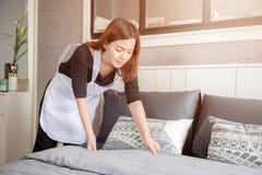 Empregada doméstica nova que ordena a cama na sala de hotel, conceito de limpeza do serviço Fotos de Stock