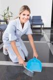 Empregada doméstica nova que varre o assoalho Imagens de Stock