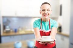 Empregada doméstica ou esposa que oferecem uma xícara de café fotos de stock