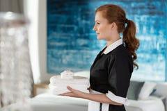 Empregada doméstica profissional que guarda toalhas foto de stock