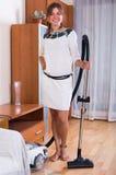 Empregada doméstica que faz a limpeza regular e que usa o hoover Imagem de Stock