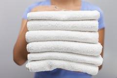 Empregada doméstica que guarda uma pilha das toalhas frescas brancas fotos de stock royalty free
