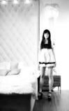 Empregada doméstica 'sexy' bonita da menina perto de uma cama Foto de Stock