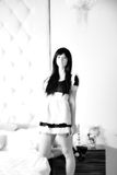 Empregada doméstica 'sexy' bonita da menina perto de uma cama Fotos de Stock