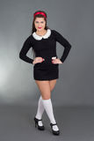 Empregada doméstica 'sexy' no uniforme preto com penteado retro Fotografia de Stock Royalty Free