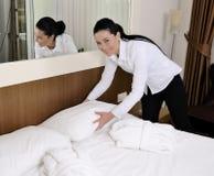 Empregada doméstica que faz a cama no quarto de hotel Fotos de Stock Royalty Free