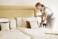 Empregada doméstica que faz a cama no quarto de hotel Foto de Stock