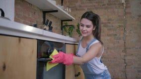 Empregada feliz, retrato da dona de casa de sorriso fêmea nas luvas de borracha durante a limpeza geral da cozinha e filme