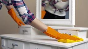 A empregada nas luvas de borracha que espanam as superfícies na sala com guardanapo especial, dona de casa limpa a casa, agregado vídeos de arquivo