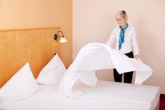 Empregada que faz a cama na sala de hotel Imagem de Stock Royalty Free