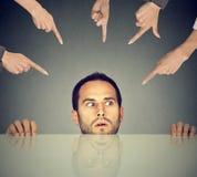 Empregado assustado do homem que esconde sob a tabela que está sendo acusada por muitos povos que apontam os dedos nele Fotos de Stock Royalty Free