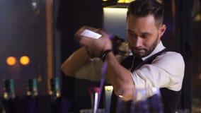 Empregado de bar à moda que chicoteia a bebida do álcool usando o abanador video estoque