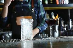Empregado de bar com cocktail alcoólico e vidro de mistura do gelo no contador imagens de stock royalty free