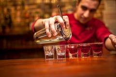 Empregado de bar com o abanador de cocktail que derrama a bebida alcoólica vermelha foto de stock royalty free
