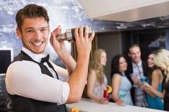 Empregado de bar considerável que sorri na câmera que faz um cocktail Imagens de Stock